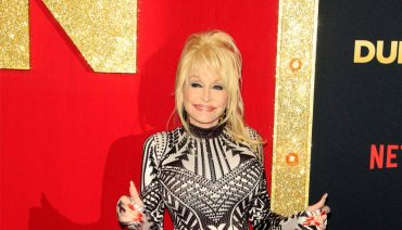 dolly parton smiling on the red carpet in a black and white dress