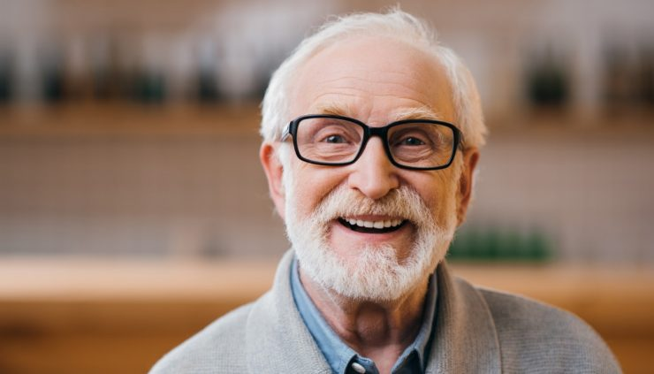 older man wearing glasses and smiling into the camera