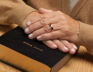 senior-with-hands-on-bible