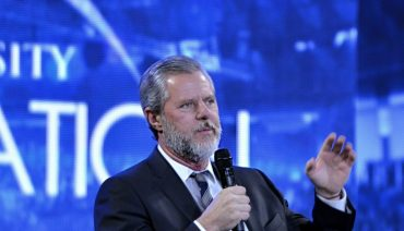 Jerry falwell jr speaking into a mic in front of a blue background
