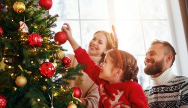 child smiling while parents watch her put a bulb on a decorated Christmas tree