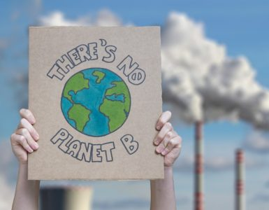 hands holding a sign saying there's no planet b in front of smoke stacks against a blue sky