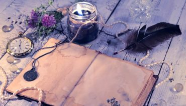 waterstained book with black candle, pearls, old watch and feather