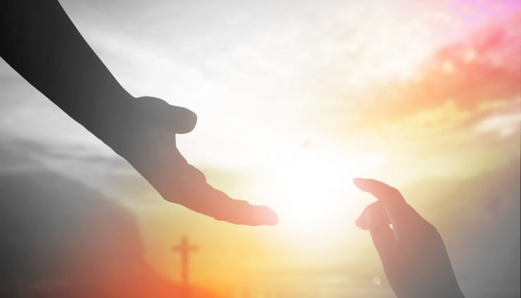 hands reaching out to touch with the setting sun and a cross in the background